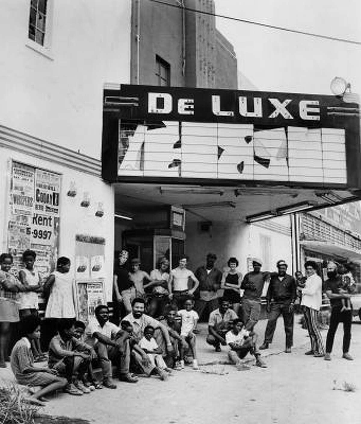 Menil staff and neighborhood volunteers, including community coordinator Mickey Leland and Menil exhibiton assistant Helen Winkler, standing second and fifth from right, gather in front of the De Luxe Theater, which they renovated in 13 days for an exhibit, in 1971.