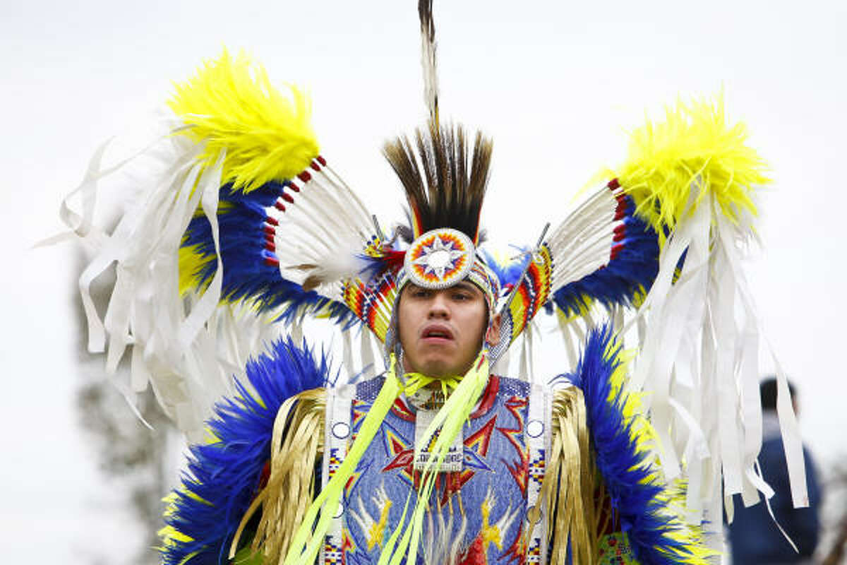 Wearing traditional Native American clothing, J.R. Lonelodge performs Sunday during the Grand Entry for the men's traditional powwow dance in Cypress.
