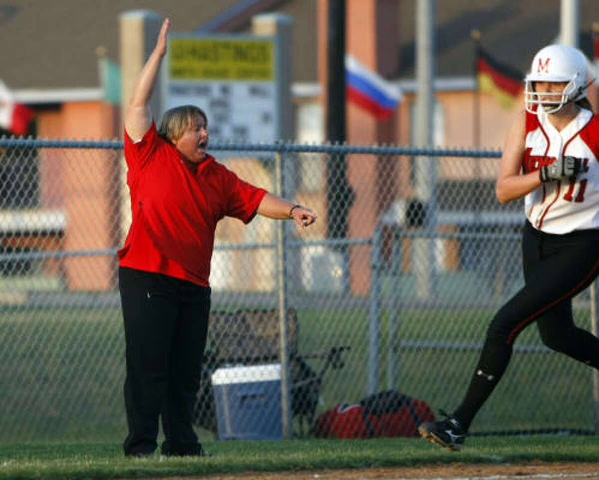 Despite the side effects of her lung cancer treatments, Memorial High School softball coach Tina Young, directing traffic at third base, guided the Mustangs into the playoffs this season with an 18-11 record.