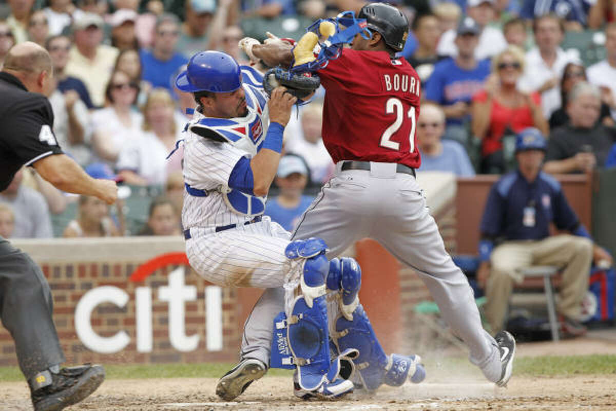 The Astros' Michael Bourn is out at home in the fourth inning as he slams into Cubs catcher Geovany Soto on Monday.