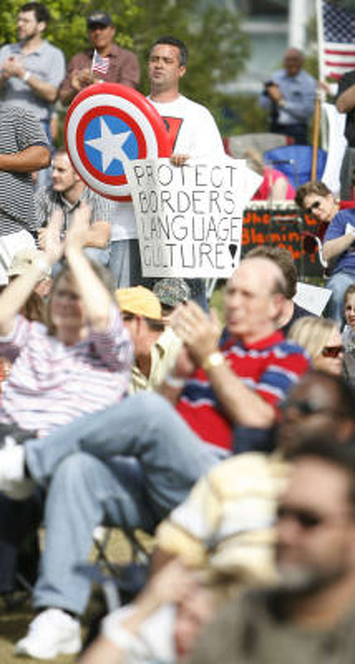 Bryan Deleon, shown holding a Captain America shield, joins about 200 other people at a tea party rally at Discovery Green Park on Thursday.