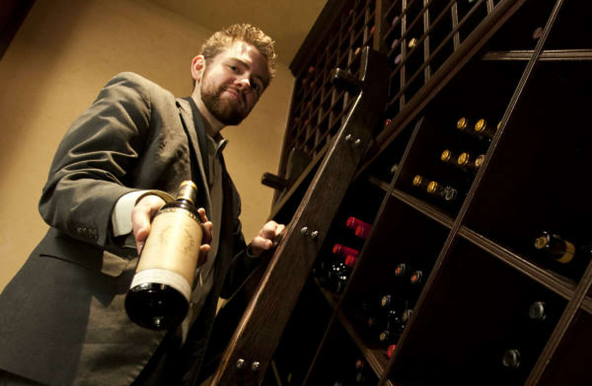 Justin Vann, wine manager at Vic & Anthony's, shows a bottle of Susana Balbo Ciros Torrentes 2009 wine in the restaurant's wine cellar.