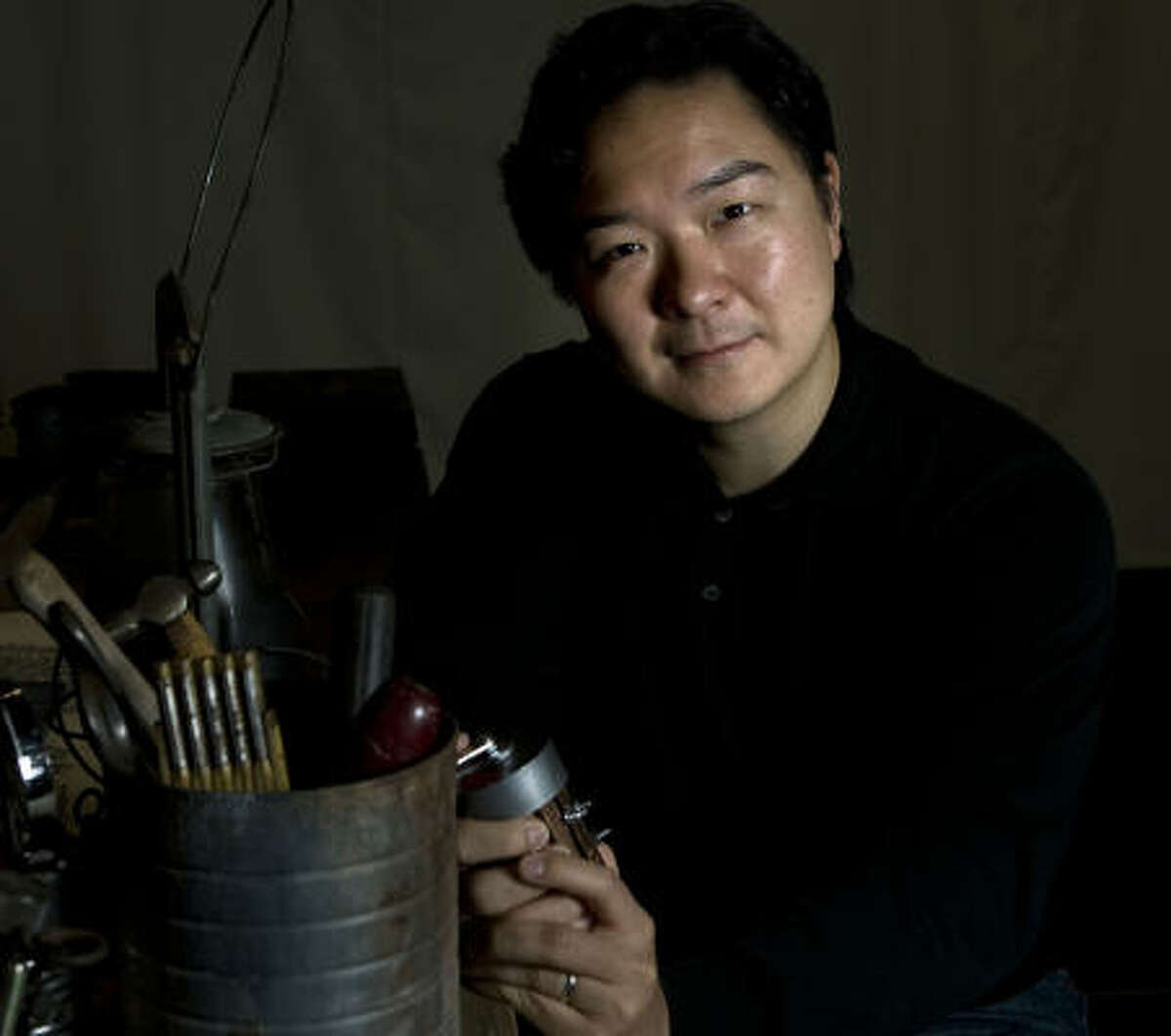 Playwright Kenneth Lin holds a model of the contraption that figures prominently in his fact-based drama, Intelligence-Slave, making its world premiere at the Alley Theatre.