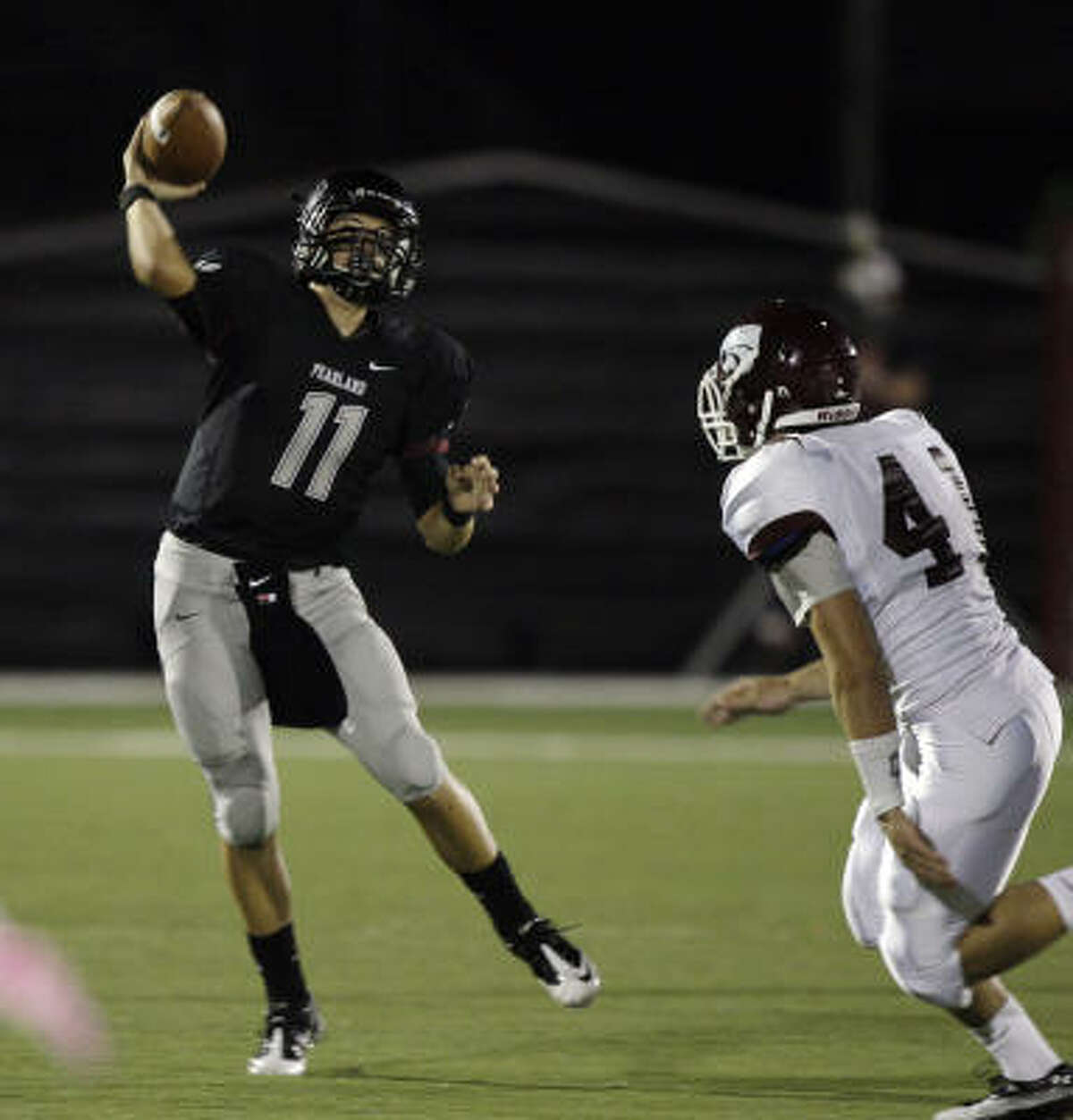 Pearland quarterback Trey Anderson fires a throw while under pressure from Clear Creek's John Payne during Friday's District 24-5A matchup at Pearland ISD Stadium.