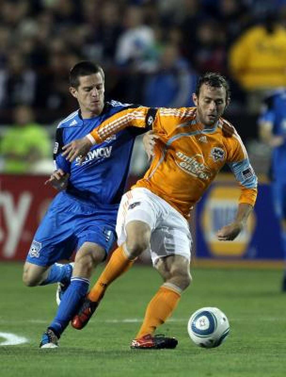 Dynamo midfielder Brad Davis holds off San Jose's Sam Cronin on Saturday night.