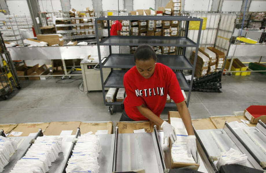 Serene Silvester stacks DVDs as they are sorted by a scanner in preparation for being shipped out at a Netflix distribution center in the Humble area. Photo: Julio Cortez:, Chronicle