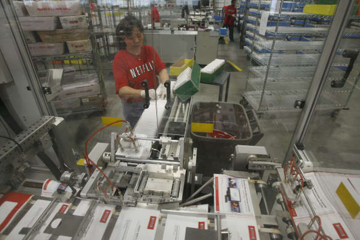 Hoa Cong works on a machine that puts DVDs into envelopes at the Netflix distribution center in the Humble area.