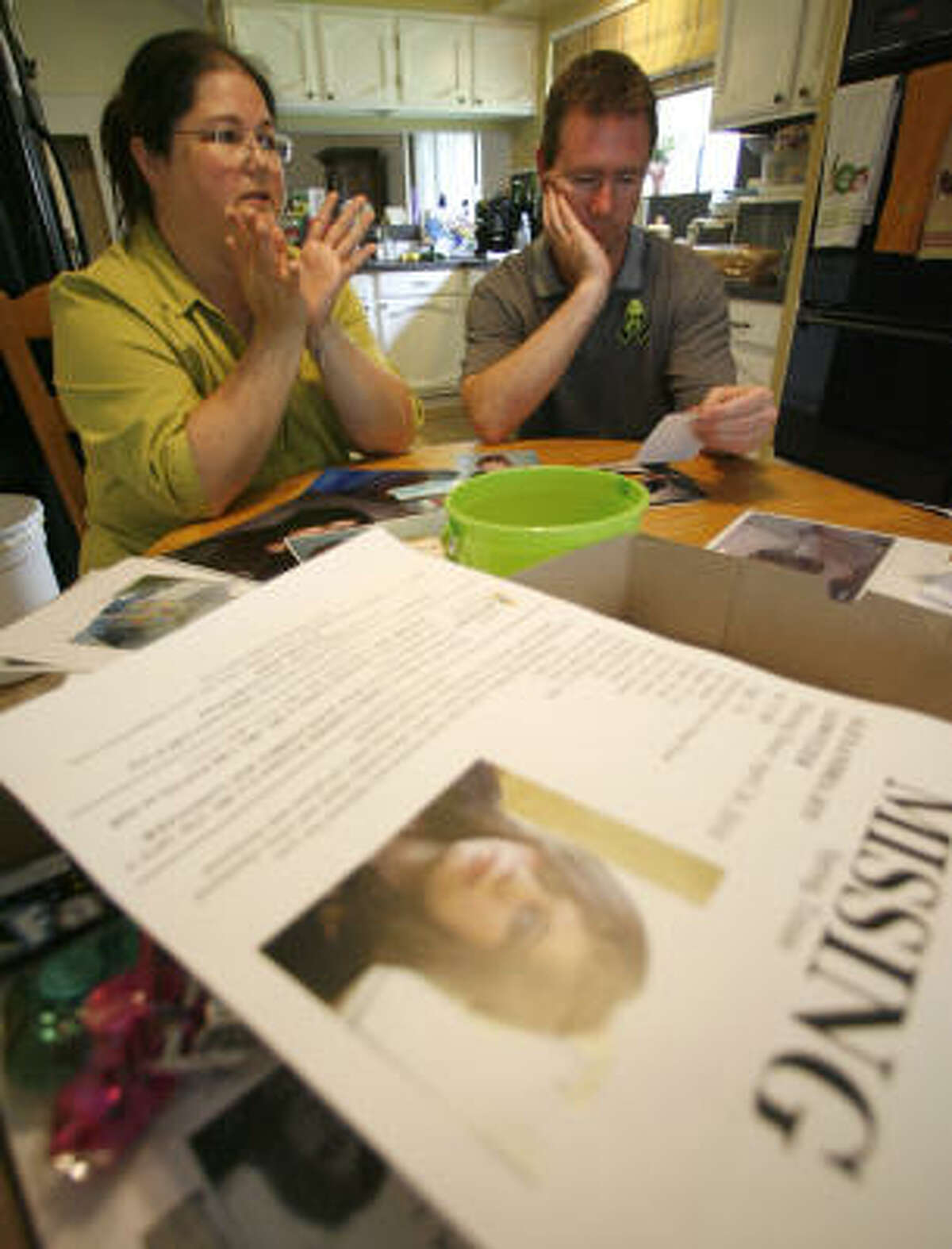 """John and JoAnn Lowitzer are surrounded by """"missing"""" posters and photos of their 16-year-old daughter, Alexandria, known as Ali."""