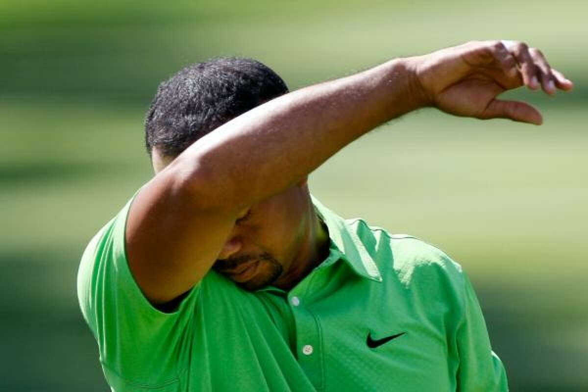 Tiger Woods wipes his face as he prepares to finish his third round on the 18th hole.