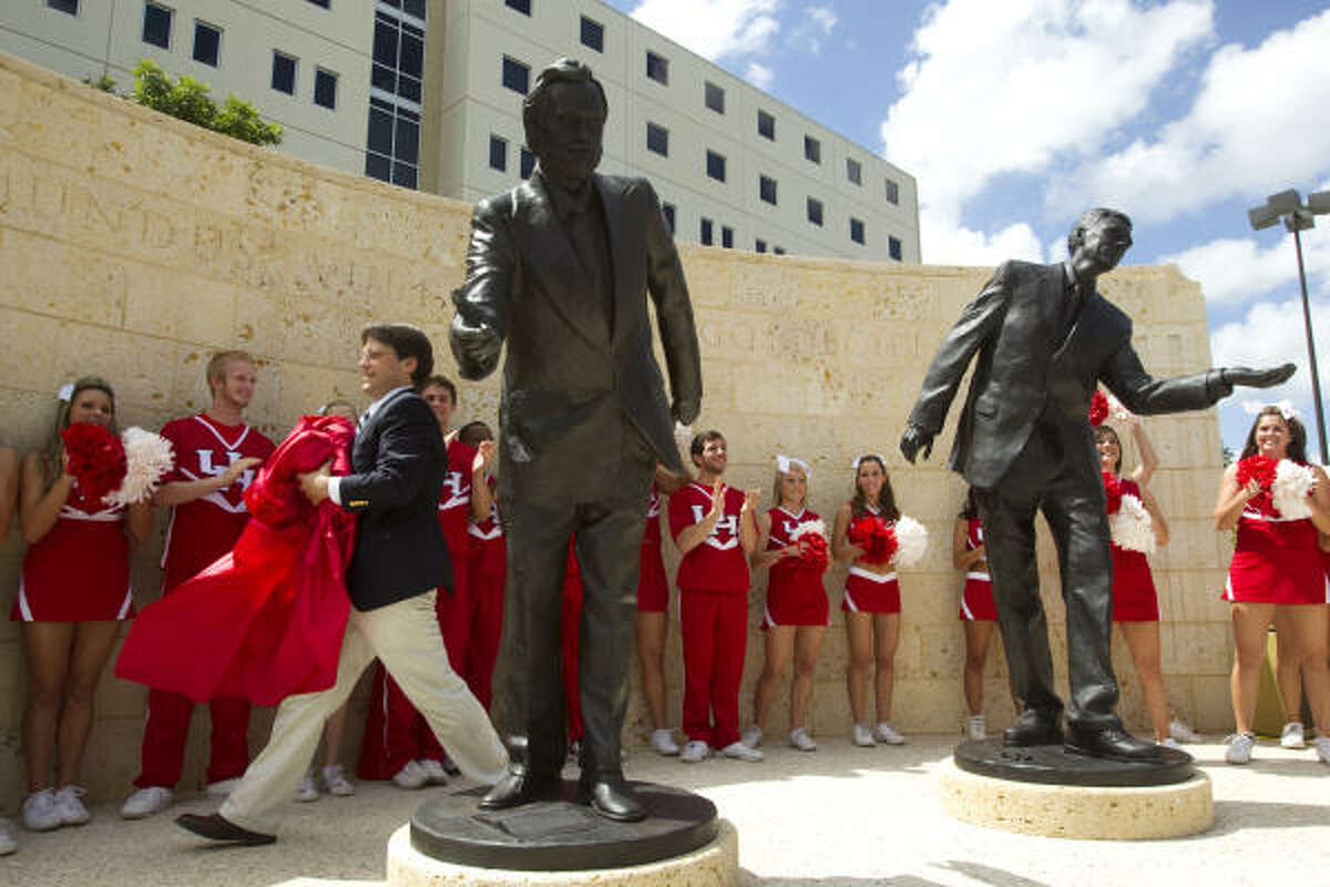 Richard Armstrong, a professor in the Honors College, walks past The Statue of Four Lies, a commissioned sculpture by The Art Guys - Michael Galbreth and Jack Massing - after he helped unveil the piece on the UH campus Wednesday.