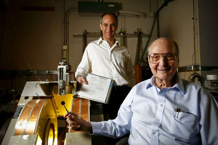 The Tootsie Pop-size magnet in Roy Weinstein's right hand is vastly stronger than a traditional copper magnet like the one next to his son, Lee, at the University of Houston. Photo: Michael Paulsen, Chronicle