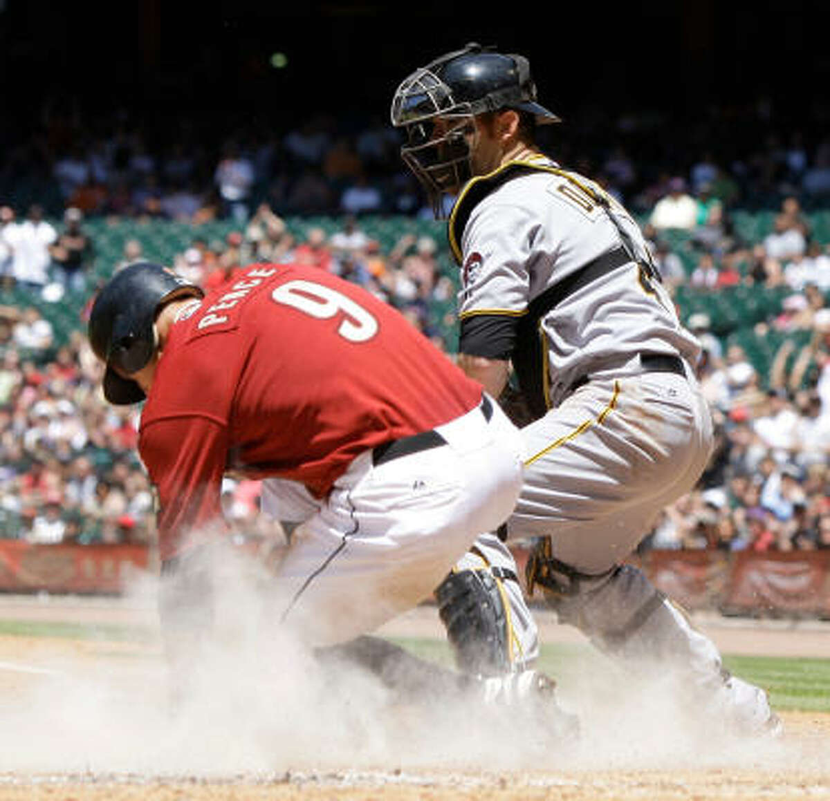 Hunter Pence scores ahead of the tag of Pittsburgh catcher Ryan Doumit on a Pedro Feliz single.