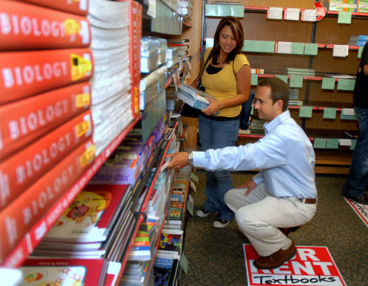Gregory Bason, district manager for Follett Higher Education Group, helps Roxanna Velasquez of Tomball find her textbooks in the Lone Star College-Montgomery Bookstore. Photo by David Hopper: For the Chronicle.