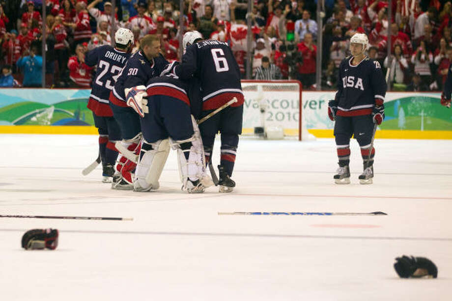 Team USA goalie Ryan Miller is consoled by Tim Thomas (30) and Erik Johnson (6) after he gave up the game-winning goal in overtime. Photo: Smiley N. Pool, Chronicle Olympic Bureau