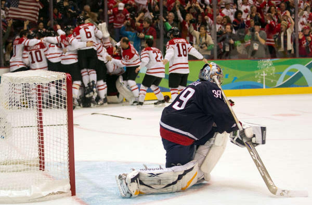 Ryan Miller looks away as Canada players celebrate.