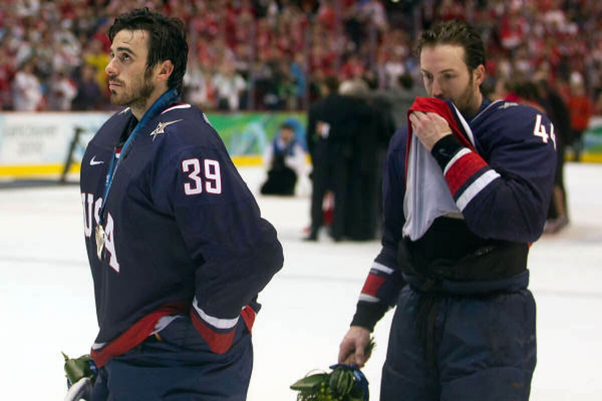 U.S. goalie Ryan Miller and teammate Brooks Orpik skate off the ice after receiving their silver medals.