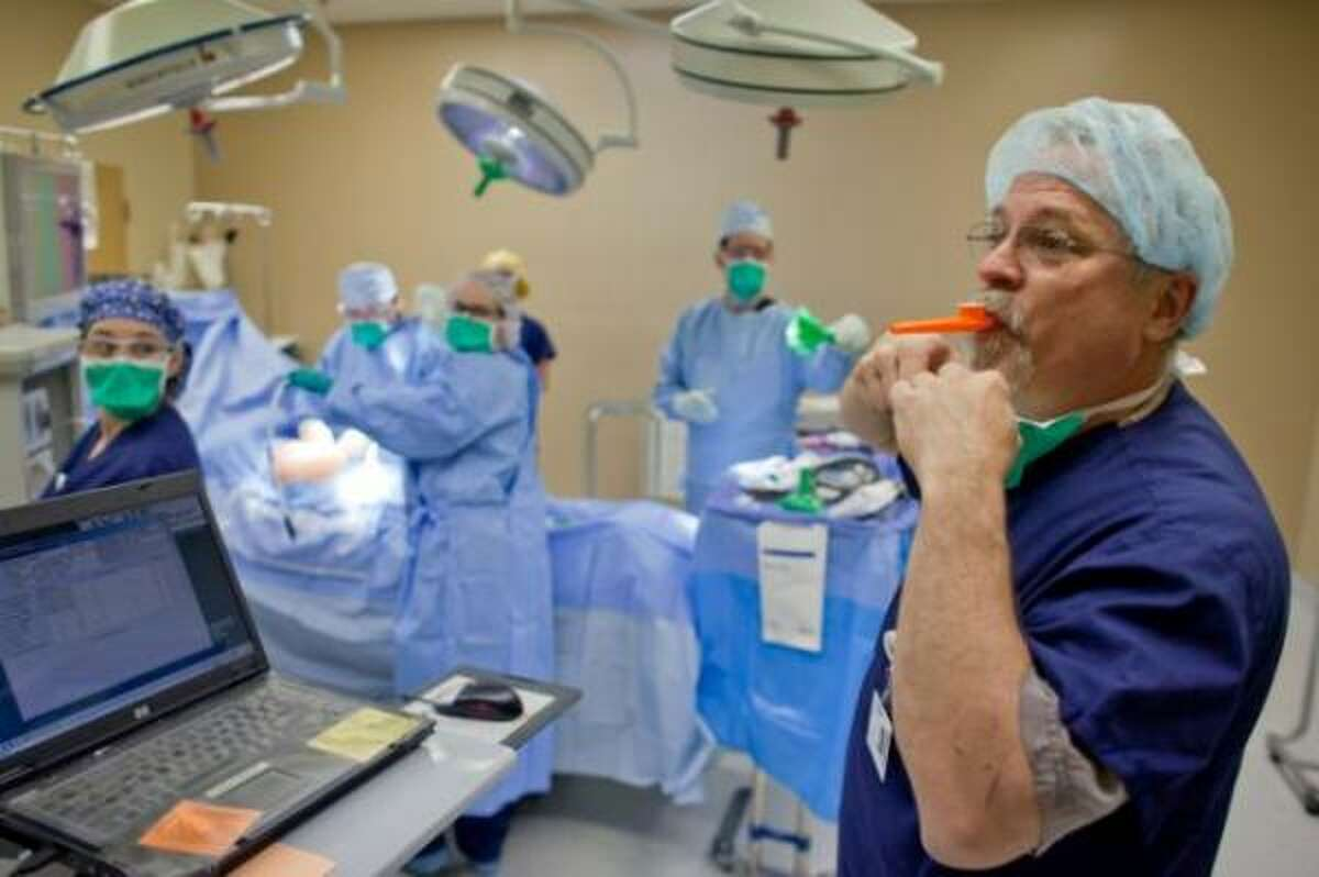 Operating room Nurse Joel Andrews blows into a kazoo, a method used by the hospital before a surgery to get the attention of the staff for the mandated time out. During time out a briefing is given and information checked before the operation proceeds. Cascade Valley Hospital in Arlington, Wash., uses the unique method to help prevent medical errors.