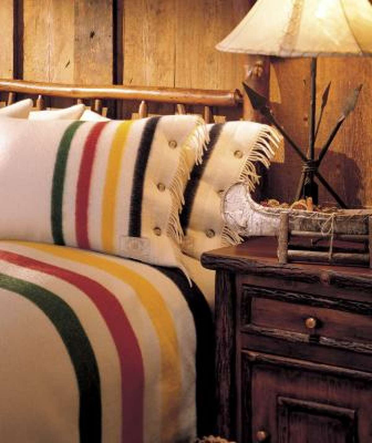 The Capote Hudson's Bay blanket and pillow sham, available at Woolrich, lend a woodsy beauty to a bedroom.