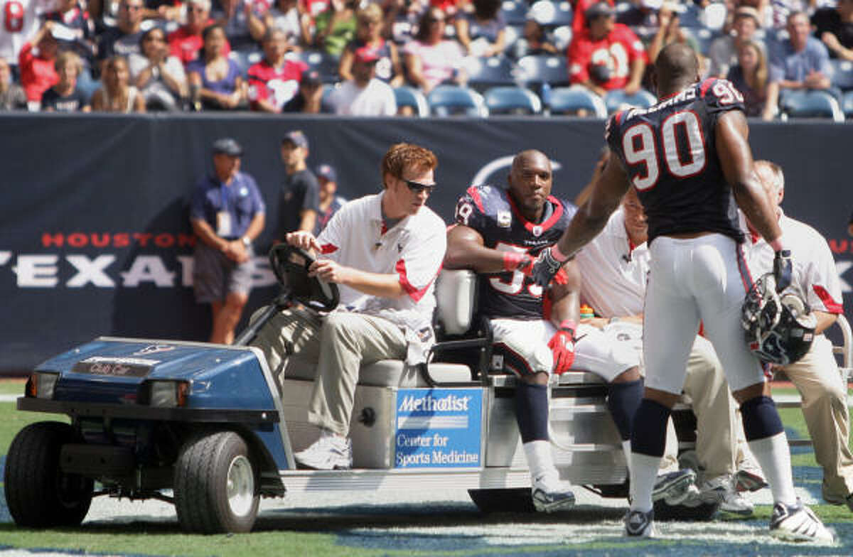 Texans defensive end Mario Williams meets Texans linebacker DeMeco Ryans on the cart as Ryans leaves the game after an injury.