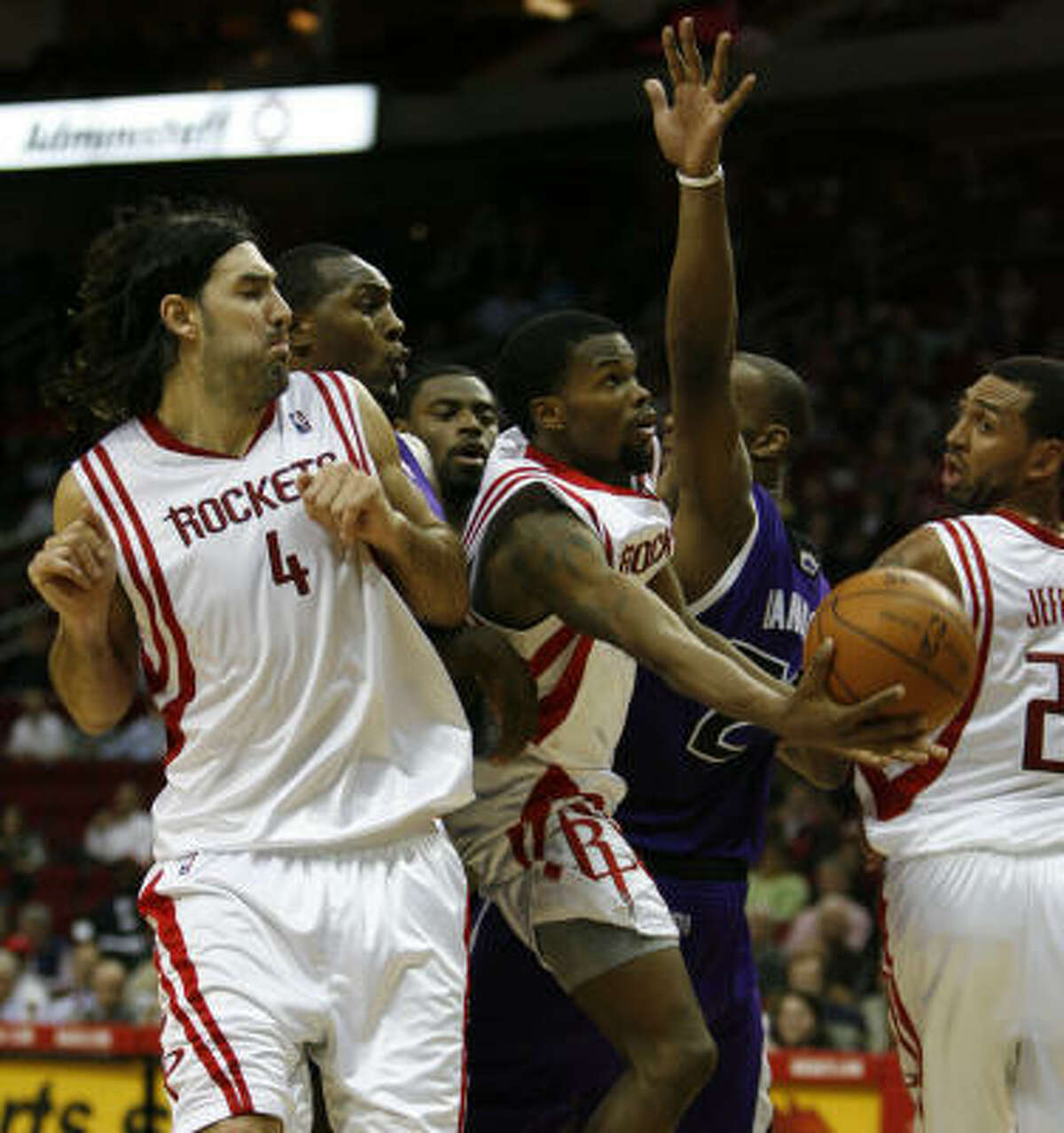 Aaron Brooks tries to squeeze through the crowd under the basket during the Rockets' loss to Sacramento.