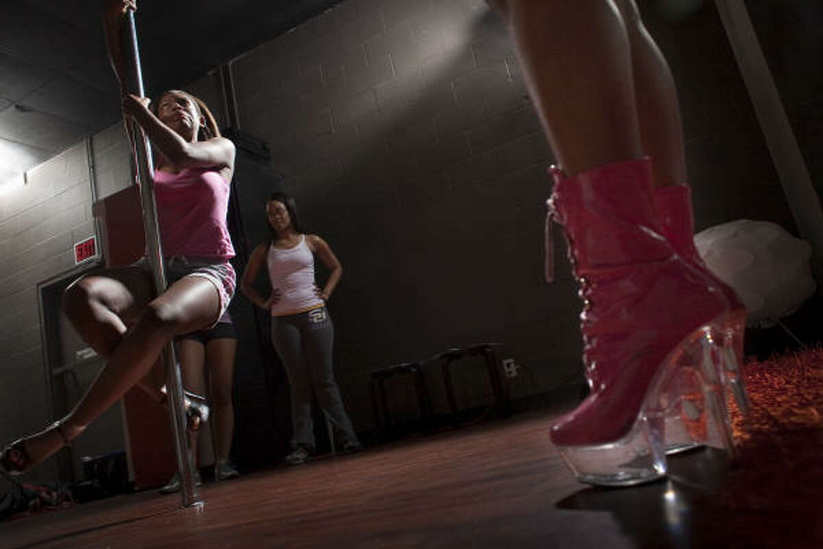 Former investment banker Nicole Phillips, right, in pink boots, instructs Alishia Terry, left during a pole dancing class as intermediate student Tche Sessum (follows her lead at Inner Me Studios.
