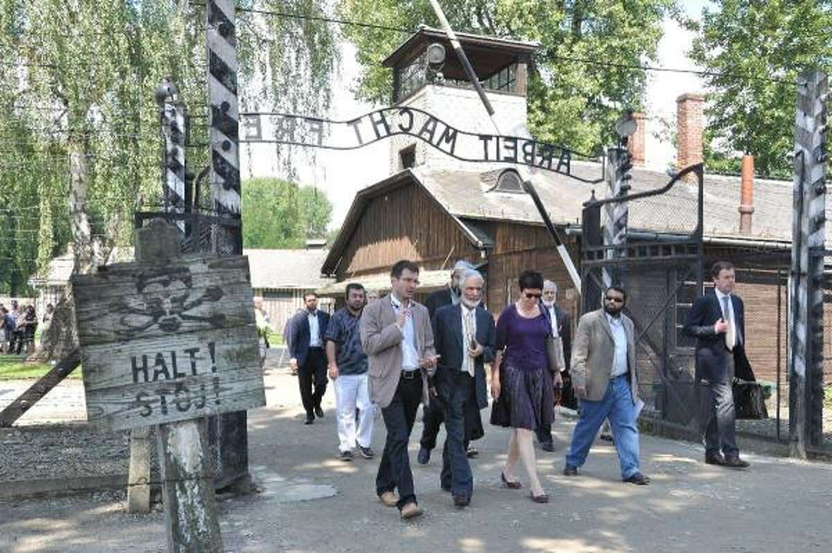 American Muslim leaders and others enter the Auschwitz concentration camp as part of a tour of Holocaust sites.