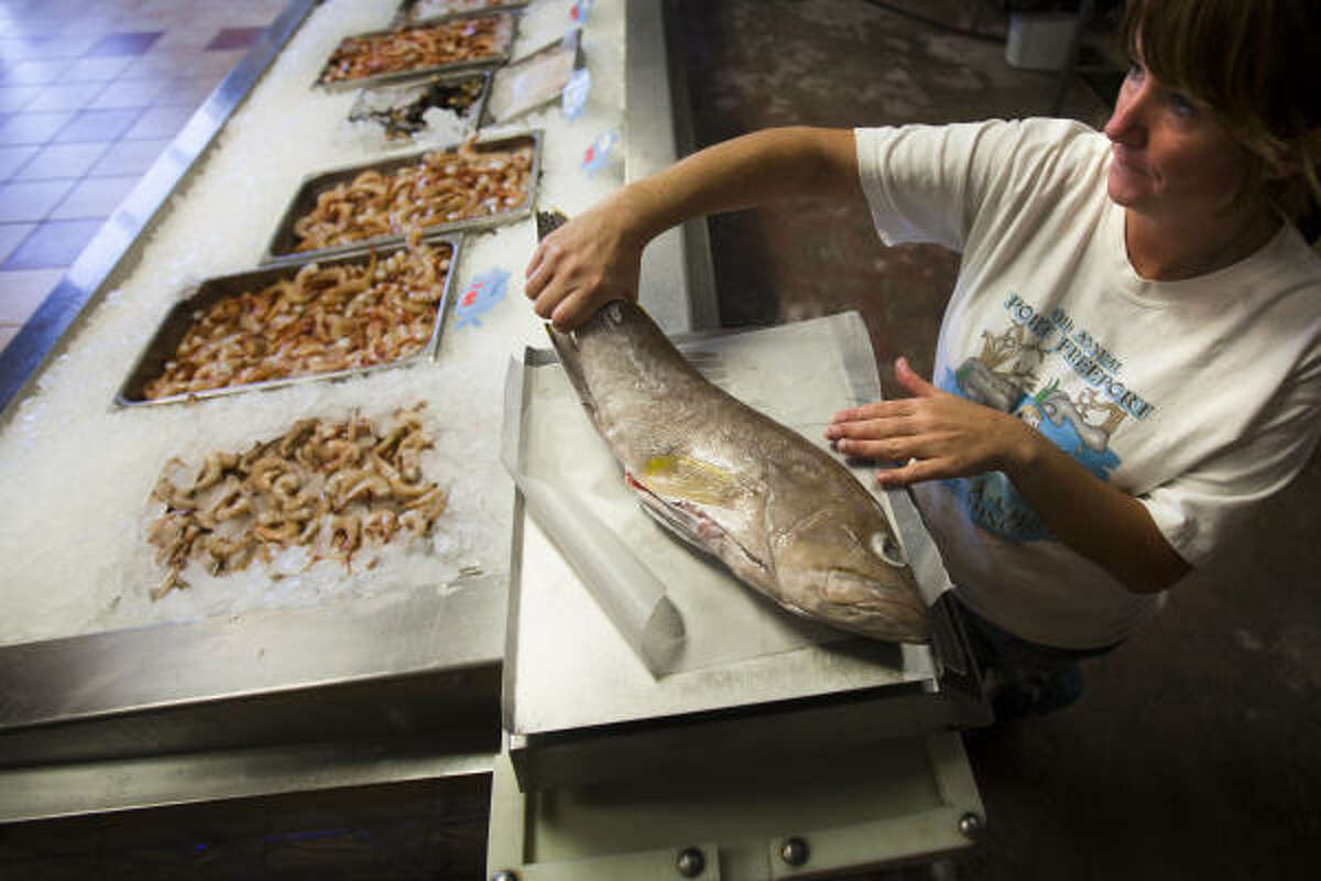 Sylia Babb weighs a fish for a customer of Captain Mark's Seafood Market, where business is off substantially.