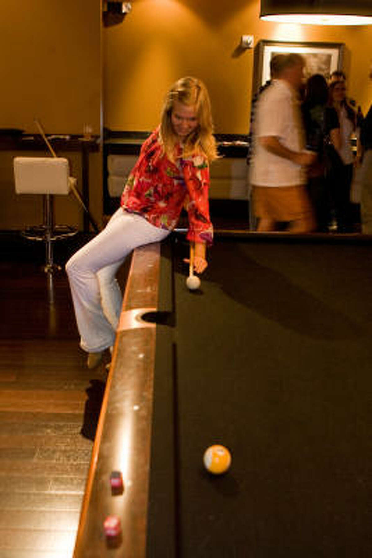 CORNER POCKET: Diana Bauhof tries for a fancy pool shot at the fundraiser.