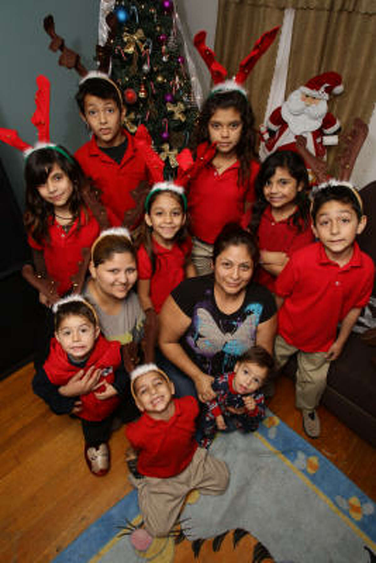 Bianca Cardenas, lower left, her five children and her brother, Aldo Perez, top left, recently moved in with her cousin, Xochitl Hernandez, lower right. The children include, clockwise from top, Josey Vasquez, 11; Maria Vasquez, 9; Angelo Mejia, 8; Leonardo Mejia, 1; Victor Mejia, 5; Alex Mejia, 2; Nayla Mejia, 7; and Maria Vasquez, 9.