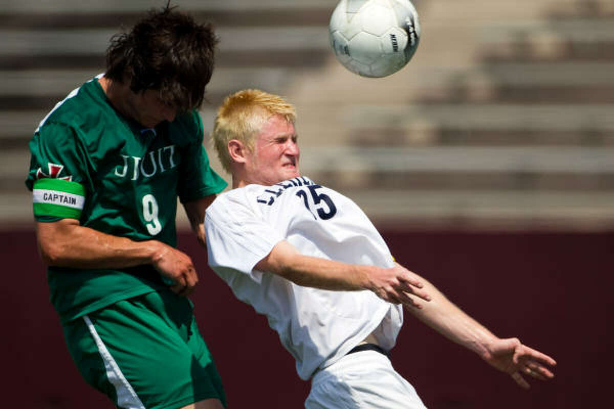 Strake Jesuit defender Beau Grenier fights for a header with Clements forward Andy McDaniel.