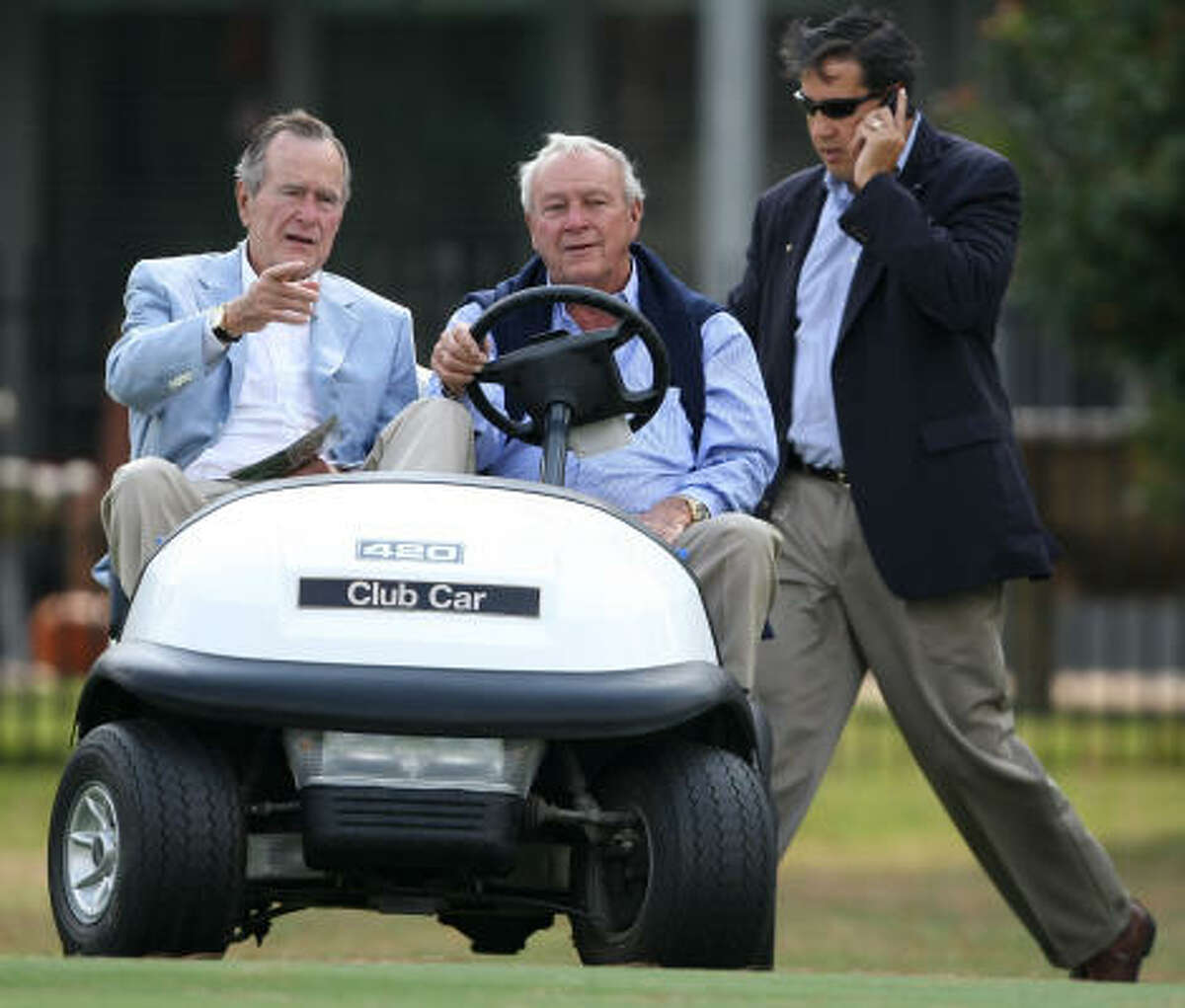 Former President George H.W. Bush, left, and golf legend Arnold Palmer watch the action from the seventh fairway during Friday's first round.