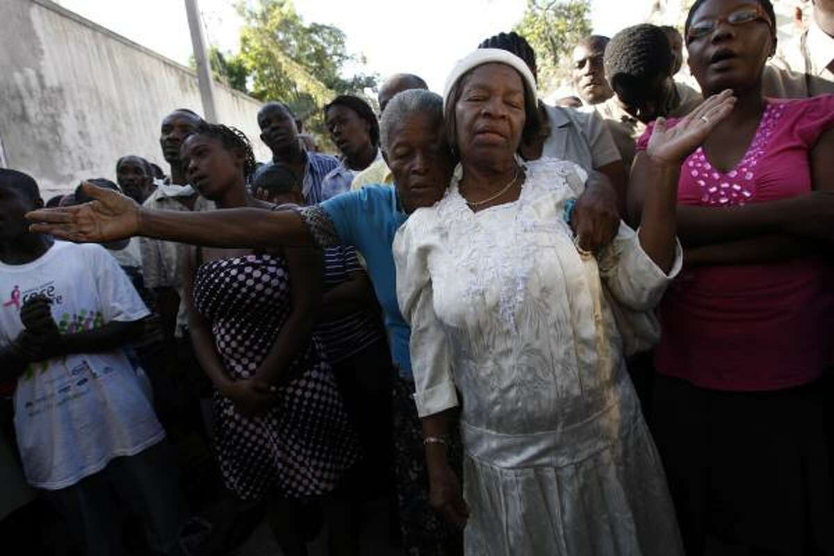 Worshippers pray Sunday during a curbside service outside the wreckage of the National Cathedral in Port-au-Prince.