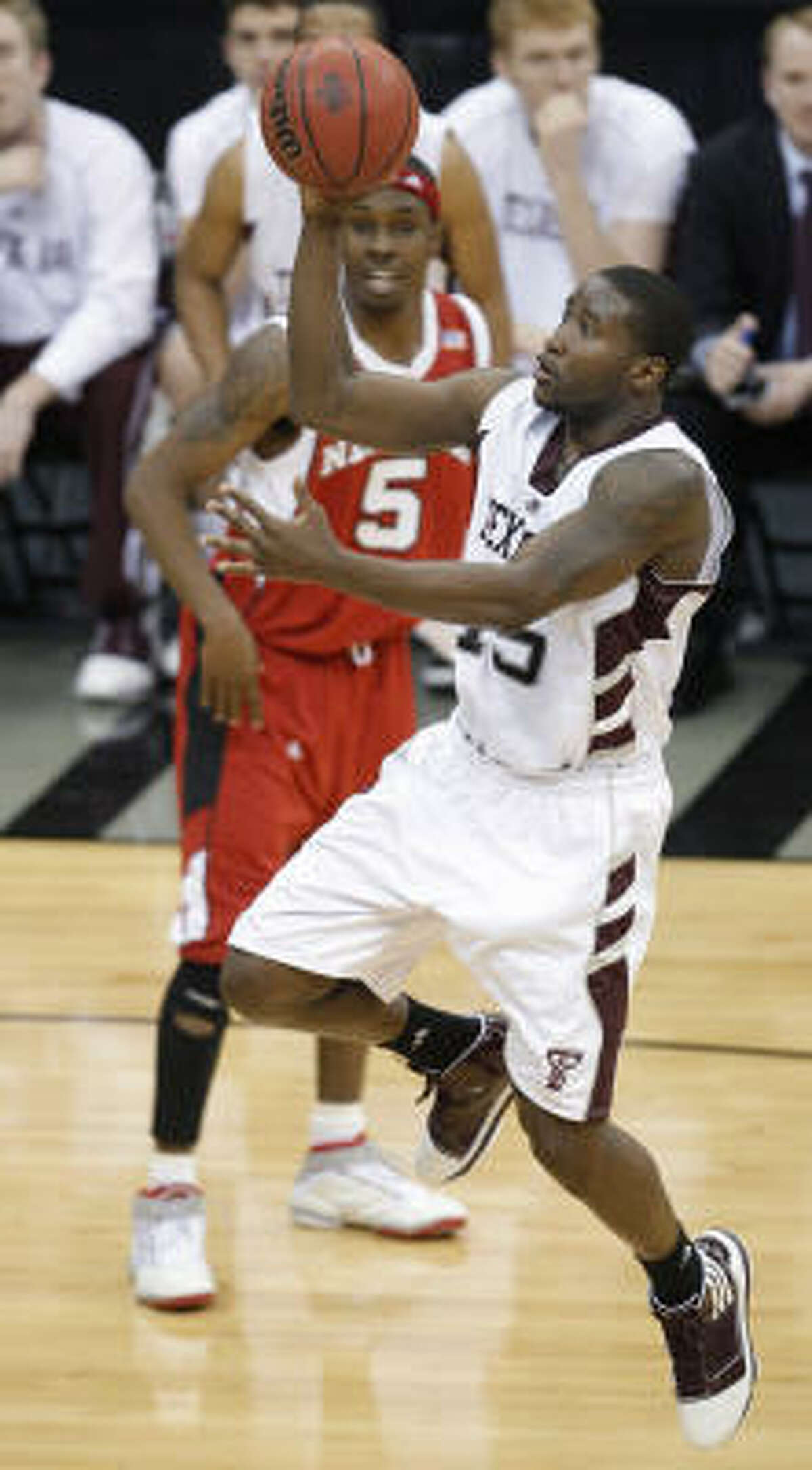Texas A&M guard Donald Sloan drives past Nebraska guard Sek Henry for two of his 23 points.