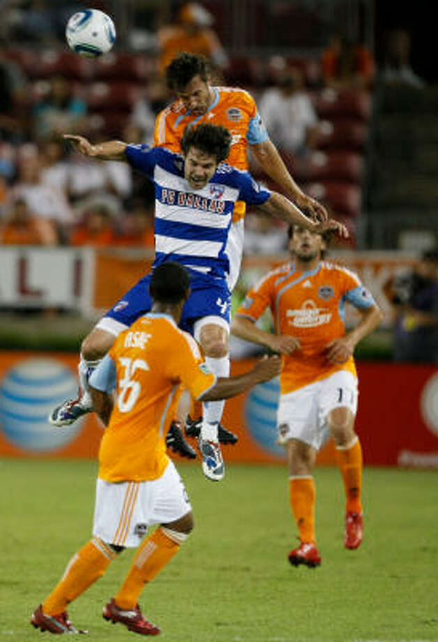 FC Dallas midfielder Heath Pearce and Dynamo defender Eddie Robinson go up for the ball in the first half. Photo: Julio Cortez, Chronicle