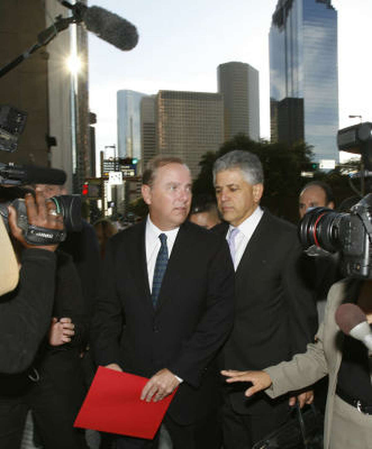 Former Enron CEO Jeff Skilling, left, shown leaving federal court in 2006 with attorney Daniel Petrocelli, is in prison for his role in Enron's downfall. On Thursday, however, the Supreme Court ordered a lower court to review his convictions.