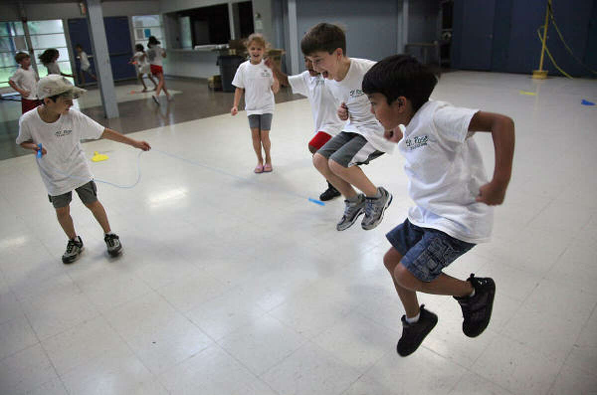 Playing helicopter, Noah Needle, 8, left, swings a rope that Ethan Nieto, 7, from right to left, Alex Martinez, 6, and Liliana McInnis, 7, jump to avoid on Thursday during Summer Safari Camp at St. Rose of Lima Catholic School in Houston.