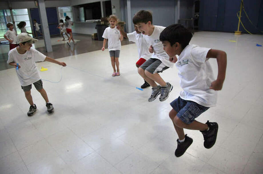 Playing helicopter, Noah Needle, 8, left, swings a rope that Ethan Nieto, 7, from right to left, Alex Martinez, 6, and Liliana McInnis, 7, jump to avoid on Thursday during Summer Safari Camp at St. Rose of Lima Catholic School in Houston. Photo: Mayra Beltran, Chronicle