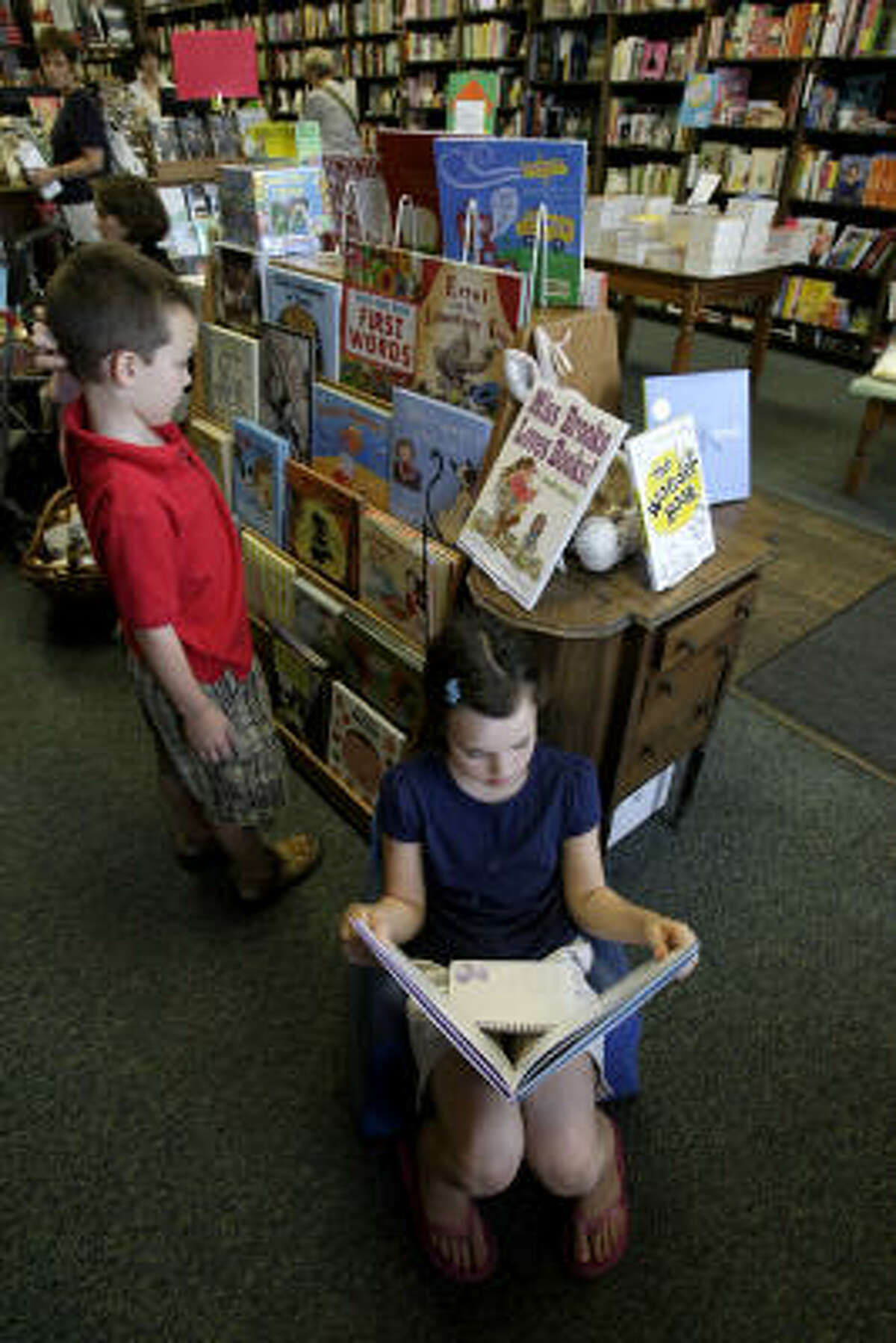 Kiley Hatch, 9, and her brother John Austin Hatch, 7, spend some time at the west Memorial area's Blue Willow Bookshop, which is having a strong year.