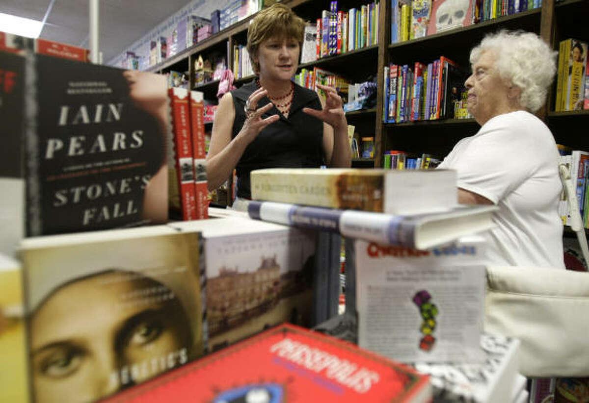 Blue Willow Bookshop owner Valerie Koehler, left, talks with customer Charlotte Reaves.