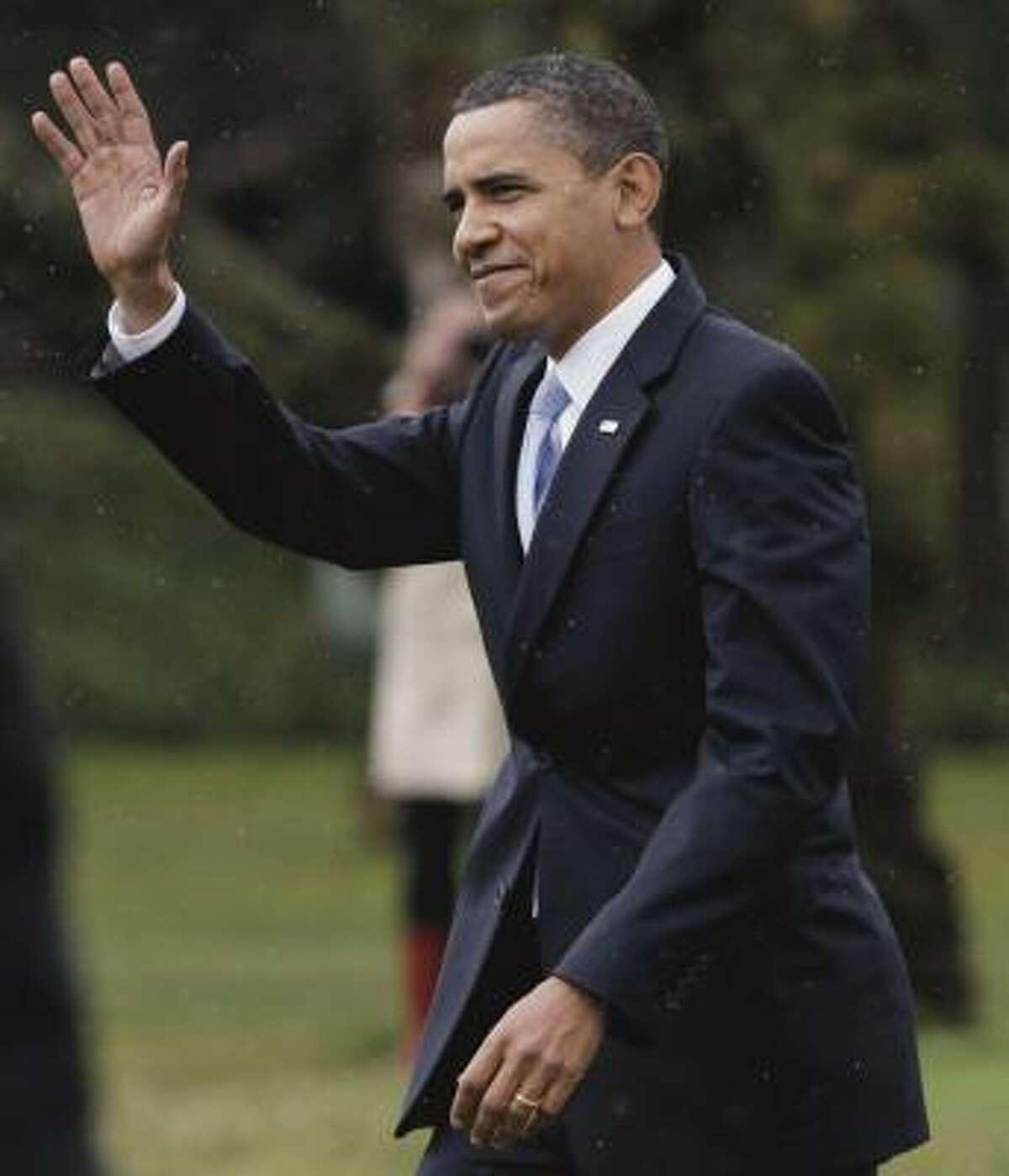 President Barack Obama walks through a light rain as he departs the White House.