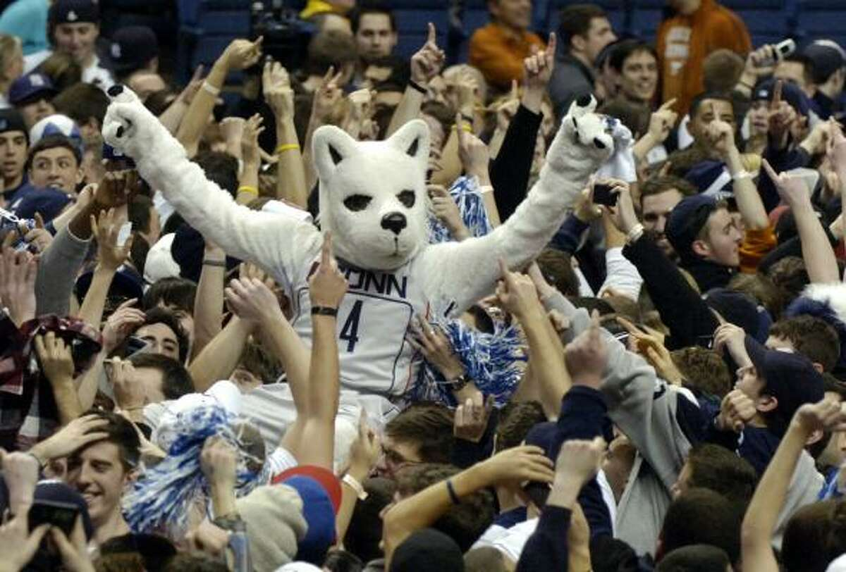 Connecticut fans celebrate with the Husky mascot on the court after Connecticut's 88-74 win over No. 1 Texas.