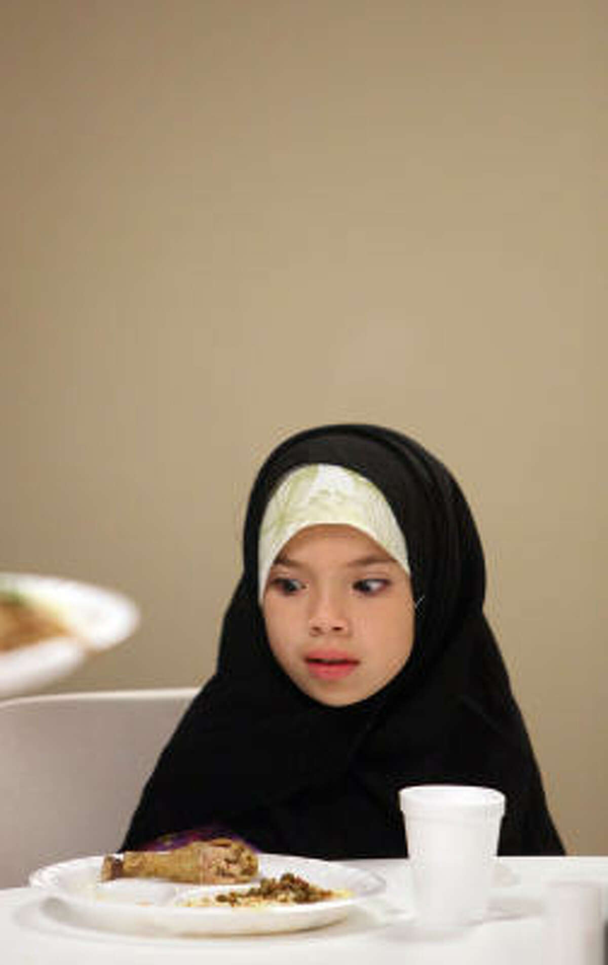 Sundos Barakat, 8, fasted for the whole day, although children are not obligated to until they reach puberty. She attended the iftar with her mother and two sisters.