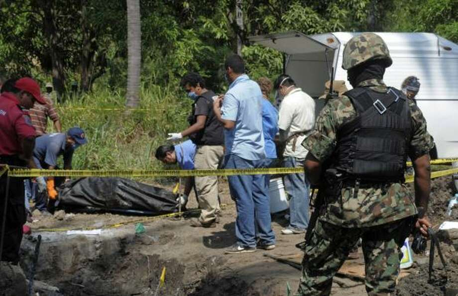 A Mexican marine stands guard Wednesday as forensic technicians remove a body from a field in Tuncingo, southern Mexico. Photo: Bernandino Hernandez, Associated Press