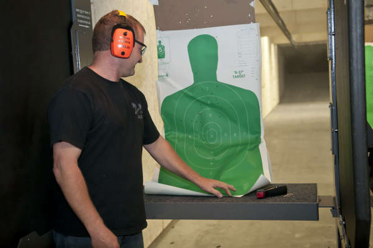 The Arms Room's Frank Laskoskie checks out his target after shooting a AK 47 at the newly opened state-of-the-art gun shop and firing range in League City. Kim Christensen: For the Chronicle.
