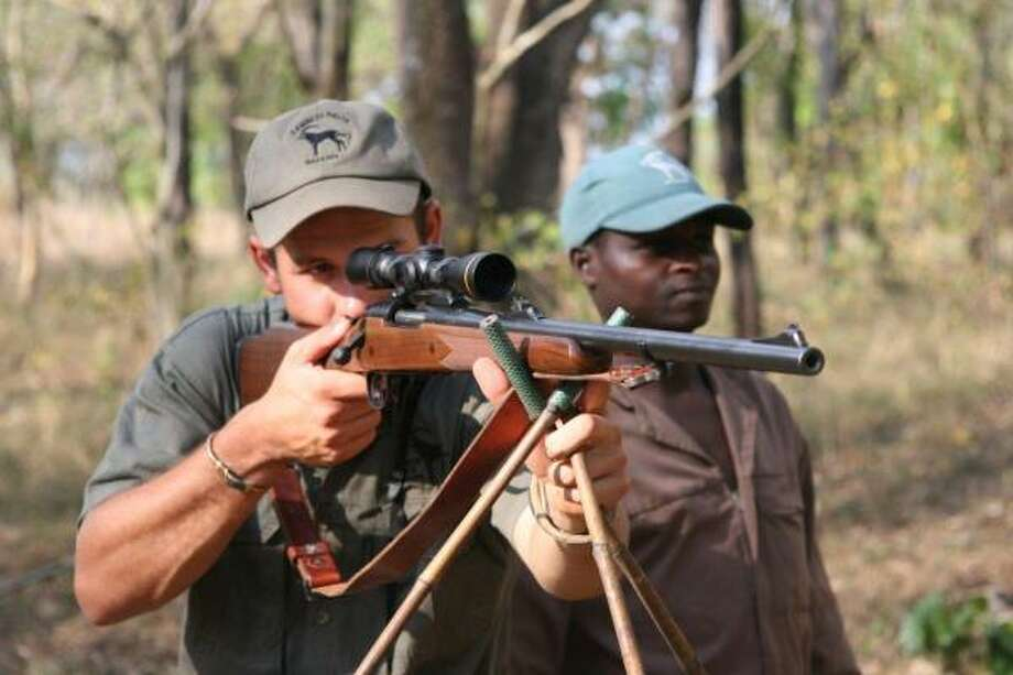 Professional hunter Poen van Zyl uses low scope power and stable shooting sticks for a close shot through the thick brush of Mozambique. Photo: Joe Doggett, For The Chronicle