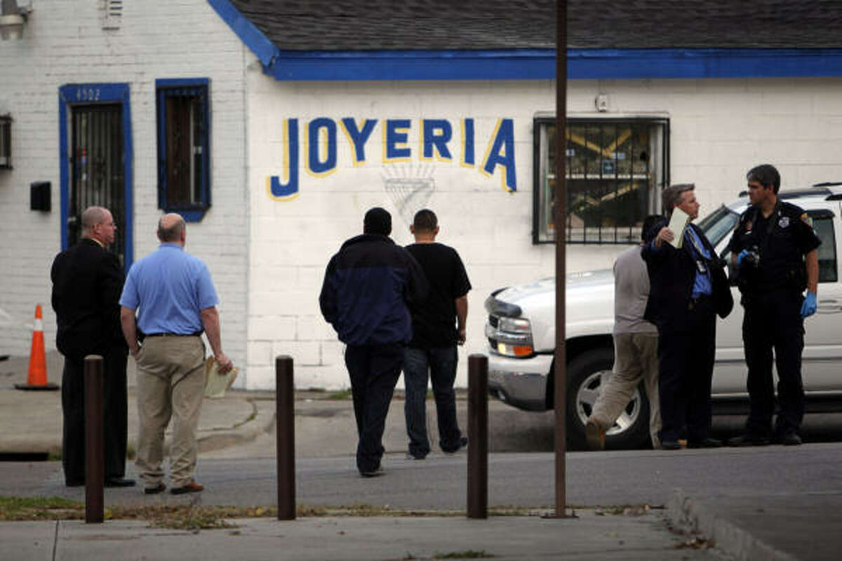 Police officers and detectives investigate the shooting of three suspected robbers by a jewelry store owner at his store east of downtown Houston Thursday, Dec. 16, 2010.