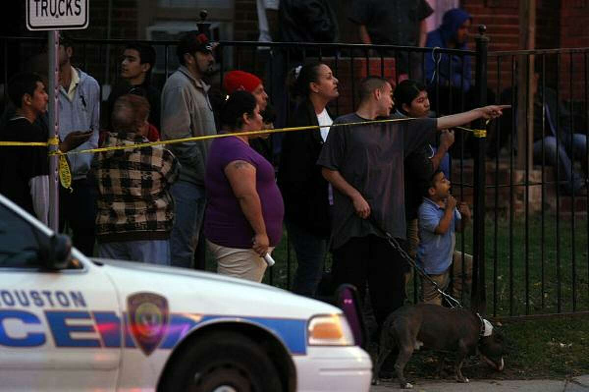 Neighborhood residents look on as HPD officers and detectives investigate the shooting of three suspected robbers by a local jewelry store owner at his store on the corner of Canal and Super east of downtown Thursday, Dec. 16, 2010, in Houston.