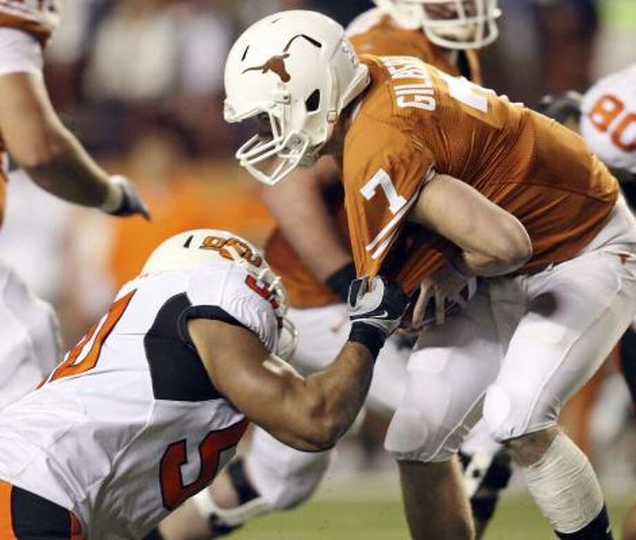 Texas Longhorns quarterback Garrett Gilbert is sacked by Oklahoma State's Jamie Blatnick on Saturday night. Photo: EDWARD A. ORNELAS, SAN ANTONIO EXPRESS-NEWS