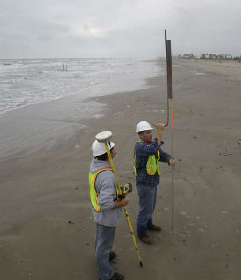 Matt Radosz, left, and Joni Hershberger, both of Weeks Marine, a contractor hired by the General Land Office, put down markers along the beach on Galveston Island. Photo: Julio Cortez, Chronicle