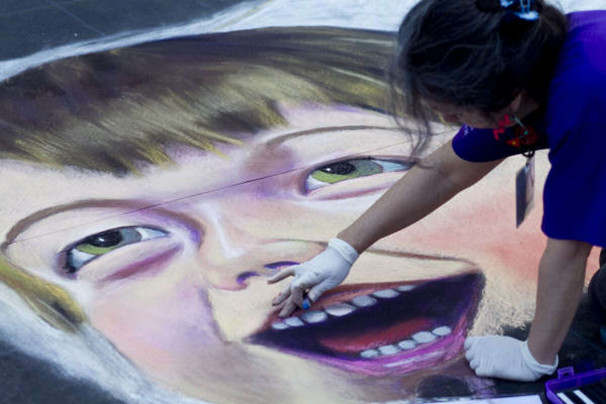 Lilibeth Andre works on a 30-by-60-foot collaborative mural at the Via Colori Street Painting Festival in downtown Houston on Saturday.